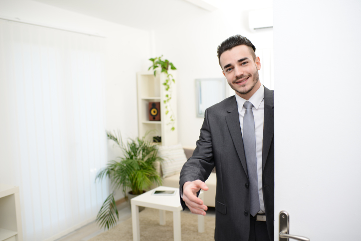 Image of young businessman at doorway giving hand to customer